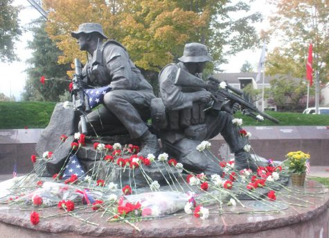 "Visitors laid flowers and triangular-folded American flags on ""The Guardian"" statue. Photo by Kelsey Lu"