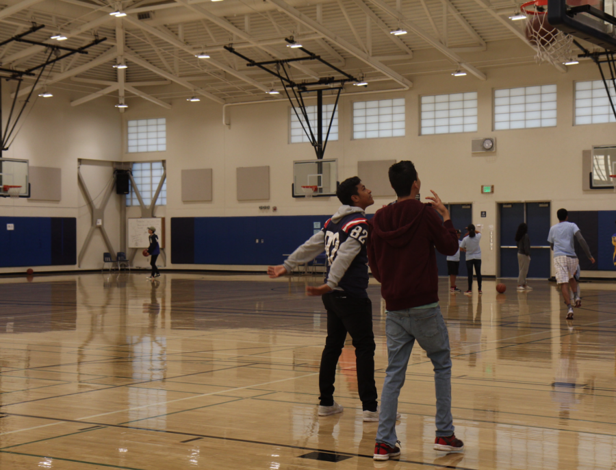 Junior Jonathan Leslie plays basketball with senior Enereo Gonzales, an ACT student, during the first period PE Inclusive class.