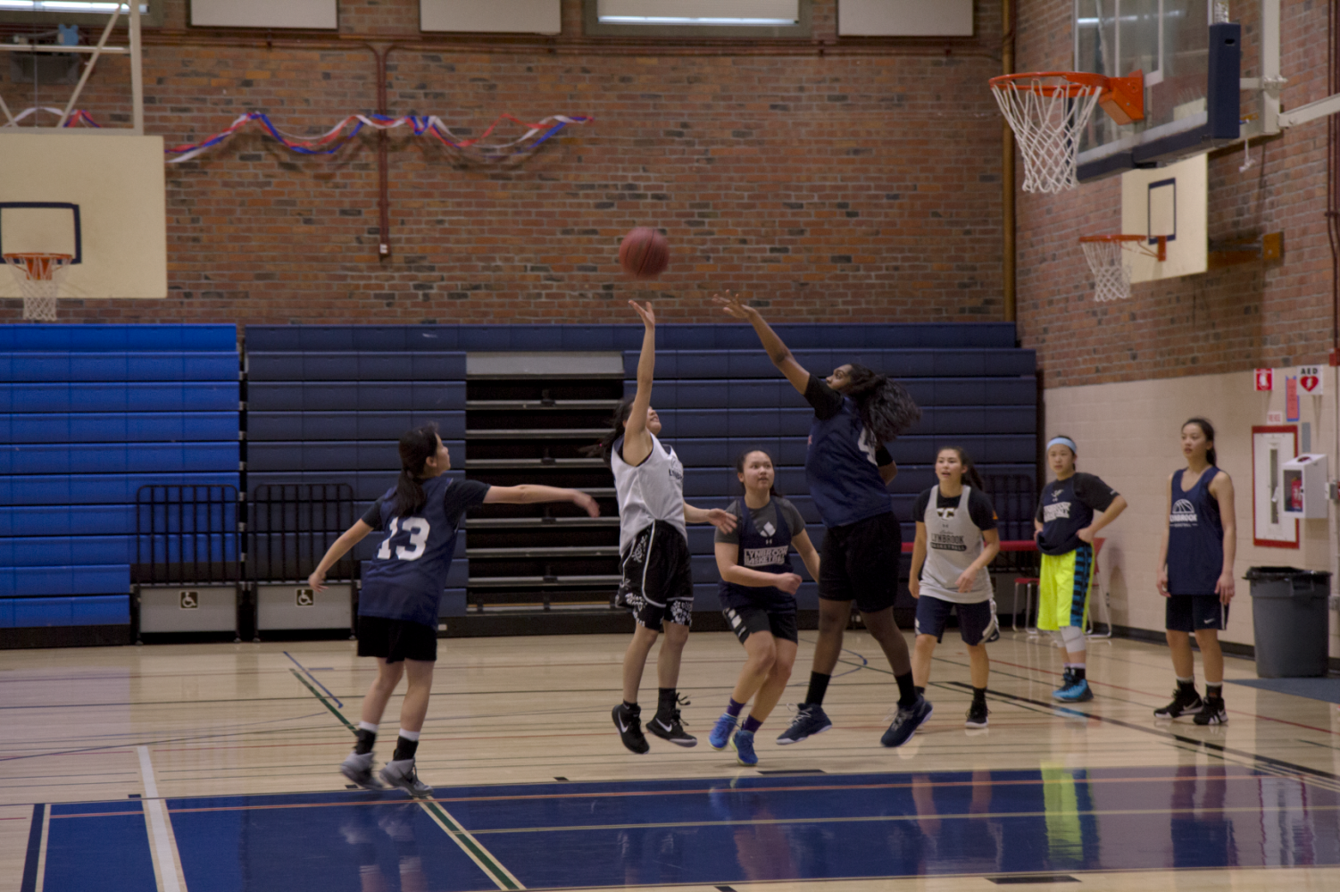 Girls basketball breaks a sweat at their practice, training hard in order to play well and increase their chances of winning at each game. Their drills include shooting, passing, rebounding and scrimmaging.
