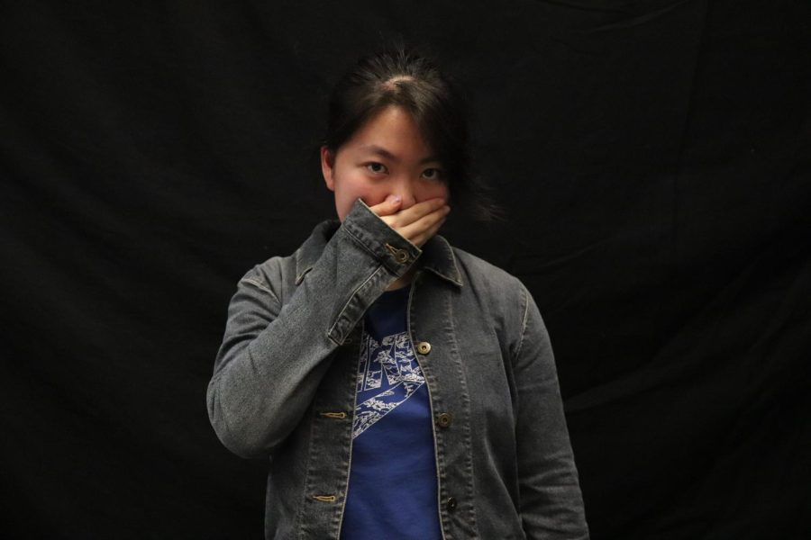 Writer Renee Ge stands with her hand over mouth, symbolizing the silences discussed in both Lulu Wang's movie