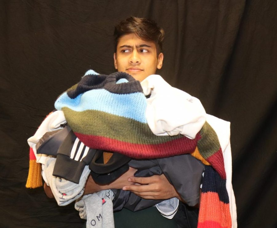 Writer Ron Aich stands with a confused expression, holding a pile of fast fashion clothes.