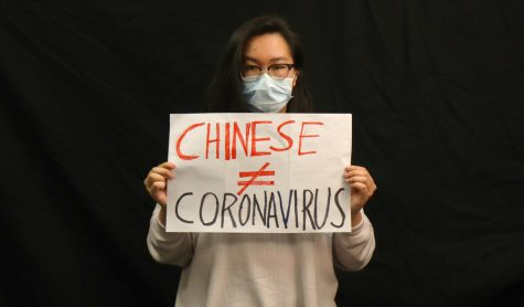 "Writer Nicole Ong stands wearing the surgical mask donned by many as protection from the newfound virus; she holds a sign saying ""Chinese ≠ Coronavirus."""