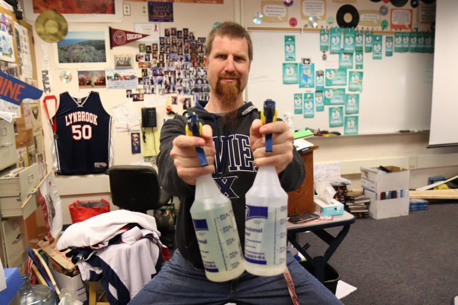 Social studies teacher Jeffrey Bale poses with bottles of disinfectant.