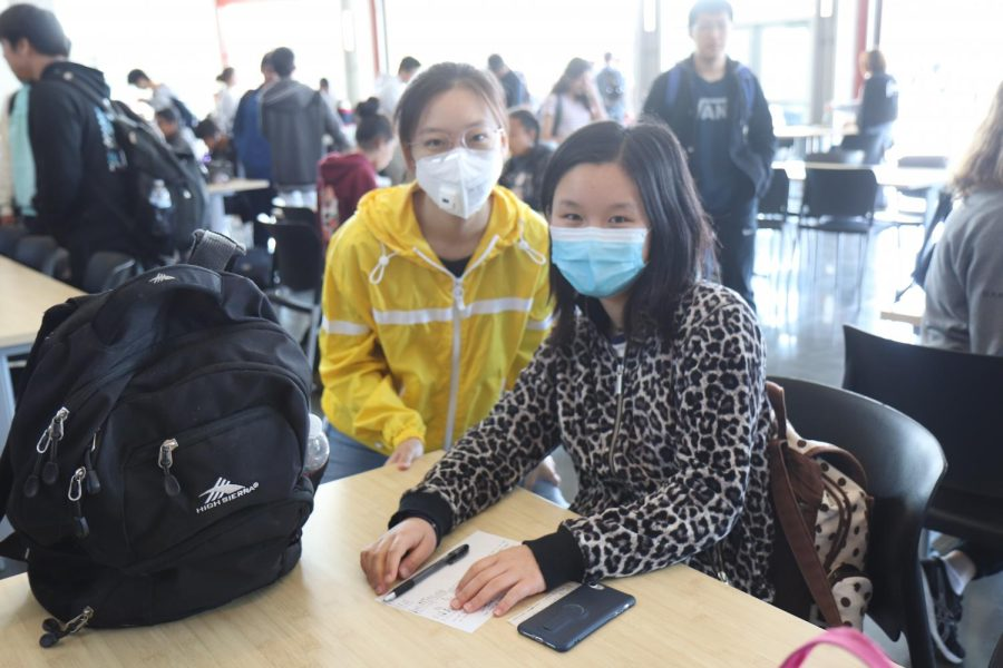 Seniors Lucy Sun and Ruijia Xing sit in the cafeteria with their masks on during brunch of Friday, March 13, the last day before the school announced its closure.