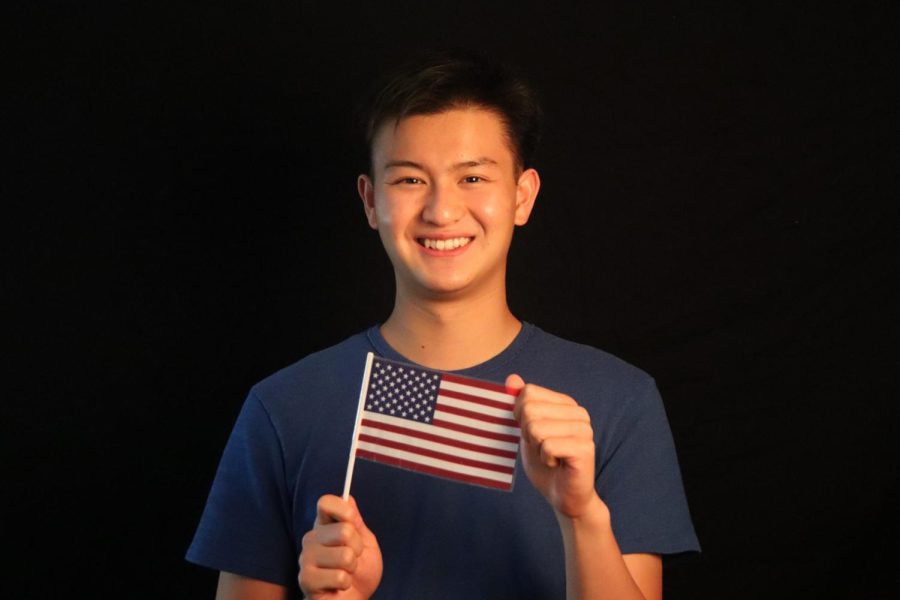 Staffer Bennie Chang holds up a mini American flag, symbolizing his love for politics.